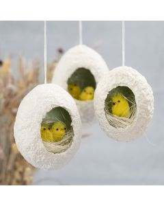 Easter eggs from papier-mâché pulp with a hole decorated with nesting chicks