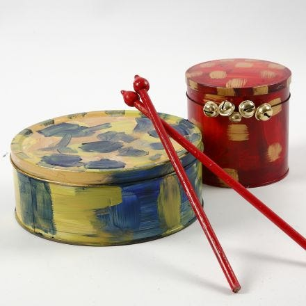 A painted Metal Tin Drum & Drumsticks made from Flower Sticks