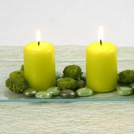 Candele lime e vetri decorativi su un piatto di vetro