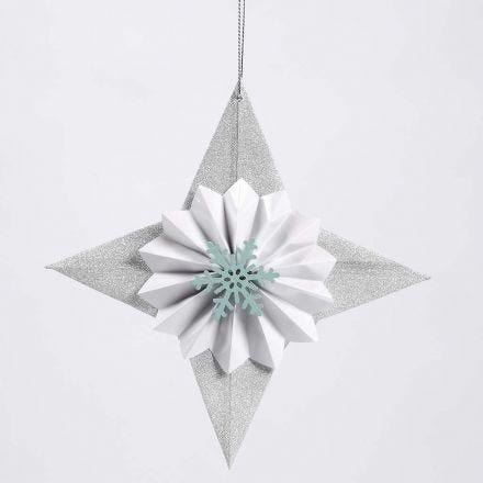 Una stella di carta glitter con una coccarda e un fiocco di neve
