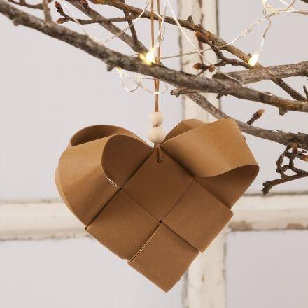 Un cestino natalizio a forma di cuore intrecciato con carta in finta pelle