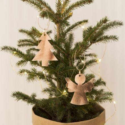Un angelo di carta in finta pelle e un albero di Natale