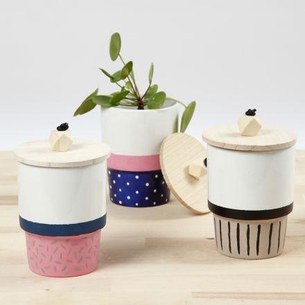 Una tazza decorata con vernice per porcellana e un coperchio con perla in legno