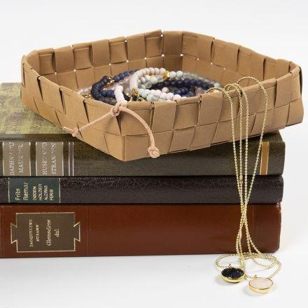 Un cestino intrecciato con strisce per stelle in carta finta pelle, fissato con un cordoncino di cuoio