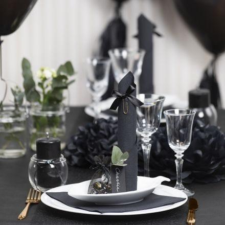 Decori da tavola neri con fiori di carta, palloncini, tovagliolo piegato e segnaposto