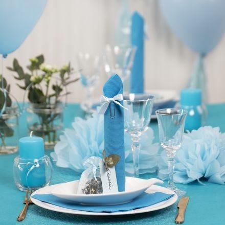 Decori da tavola azzurri con fiori di carta, palloncini, tovagliolo piegato e segnaposto