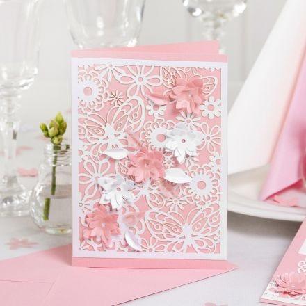 Un invito con carta fantasia in pizzo e fiori fustellati con effetto 3D