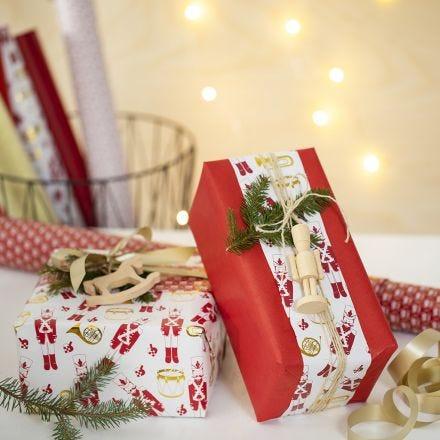 Confezione regalo di Natale creativa con due tipi di carta da regalo e una figura in legno