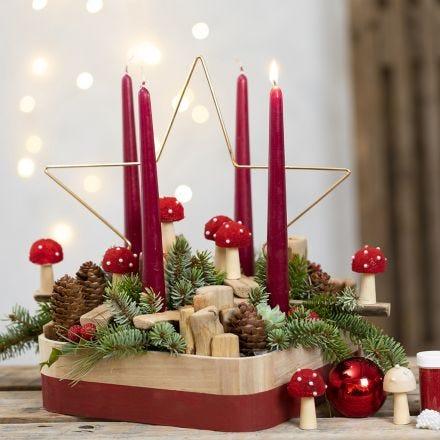 Una corona dell' avvento con stella di metallo, funghetti, abete rosso, pigne e pezzi di legno misti