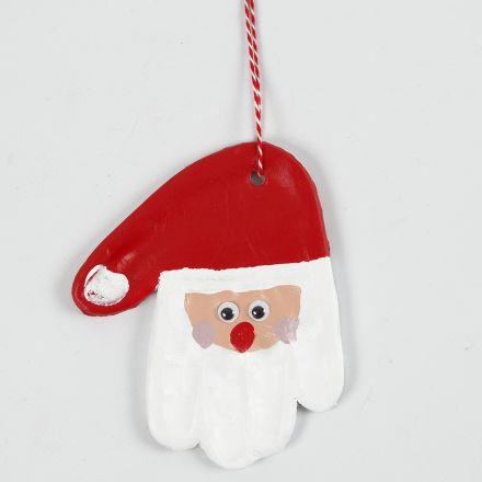 Un'impronta di mano di argilla autoindurente decorata come Babbo Natale