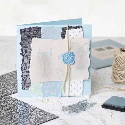 Un biglietto di auguri fatto in casa con carta fatta a mano, disegni timbrati e un sigillo cerato