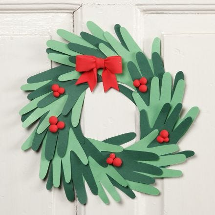 A Christmas wreath made from cut-out card hands with Silk Clay decorations