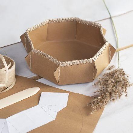 Un cestino di carta in finta pelle con un bordo di filo di carta rafia all'uncinetto
