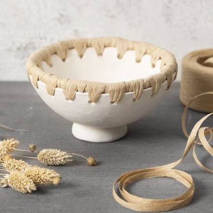 A bowl from self-hardening clay with a paper raffia rim