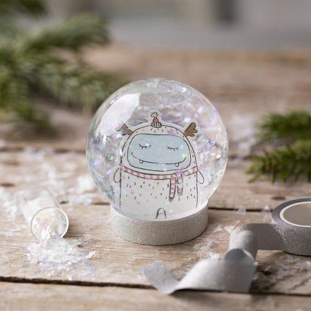 Un globo di neve con un disegno e glitter