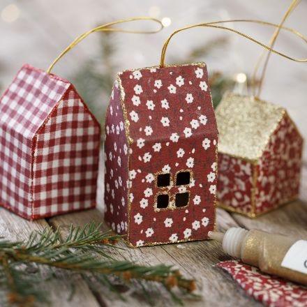 Una casa di Natale in cartoncino e stoffa decorata con glitter da appendere