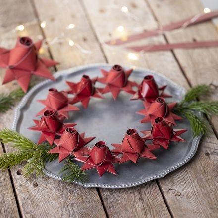 Una stella di Natale intrecciata con un bocciolo di rosa