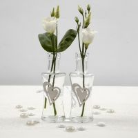 A Glass Vase with a wooden Heart secured by a white Satin Ribbon Waistband