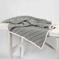 Una coperta per bebè all'uncinetto con piccoli pom pom diagonali