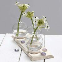 Un piccolo vaso fatto con una pallina di vetro fissata a un anello per tende.