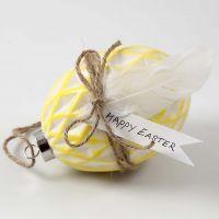 Uovo di ceramica colorato e decorato con corda naturale e piume