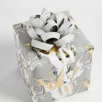 Confezione regalo decorata con una coccarda realizzata con strisce di carta per stelle