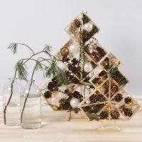 Alberi di Natale decorati con sfere natalizie, pigne, abeti e luci