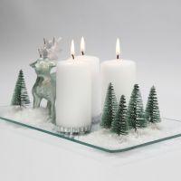 Decoro natalizio con candele, renna, alberi e neve su piatto in vetro