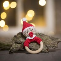 Un baby elfo all'uncinetto con un ciuccio, un cappello da elfo rosso e un pom-pom