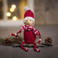 Un elfo a maglia in filato acrilico con perline di legno per mani e piedi
