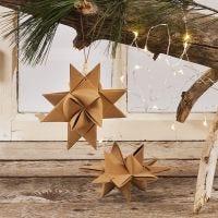 Una stella di Natale intrecciata con strisce di carta in finta pelle e cordino in cuoio con perle in legno per appenderla