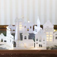 Una silhouette di città in cartoncino decorata con carta glitter e carta di velluto