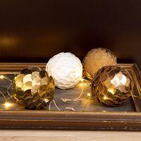 Una pallina di Natale in carta finta pelle che somiglia a una pigna