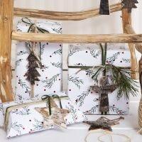 Confezione regalo natalizia con motivo di rami verdi, decorata con un pezzo di canapa naturale, nastro ed etichetta in corteccia naturale