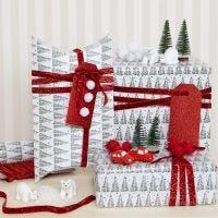 Confezione regalo natalizia decorata con pom-poms e figure in miniatura
