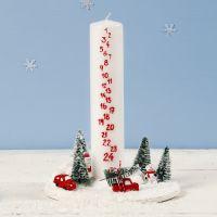 Una decorazione con candela dell'Avvento circondata da uno scenario natalizio in miniatura