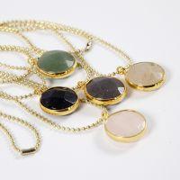 Una collana con catenella a perline e pendente gioiello con pietra