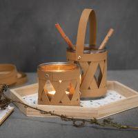 Un portacandele e un vasetto decorati con strisce di carta in finta pelle per intrecciare stelle