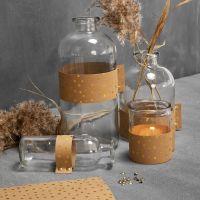 Bottiglie in vetro e portacandele decorati con carta in finta pelle