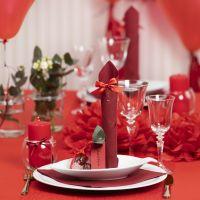 Decori da tavola rossi con fiori di carta, palloncini, tovagliolo piegato e segnaposto