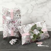 Scatolette a cuscino decorate con fiocco rosa, anello di metallo e ritagli di fiori in cartoncino