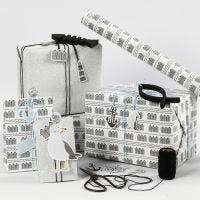 Confezione regalo bianca, nera e argento glitter con etichette in cartoncino, pesce in legno e shaker clip