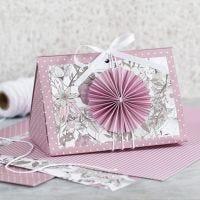 Scatola regalo rosa con coccarda e carta fantasia