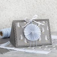 Scatola regalo blu scuro decorata con coccarda e carta fantasia