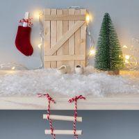 La porta di un elfo di bastoncini del ghiacciolo con una scala di corda e una cassetta delle lettere a calza di Natale