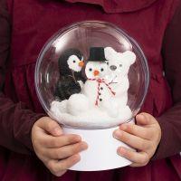 Una pallina trasparente su supporto con un pupazzo di neve, un pinguino e un orso polare all'interno