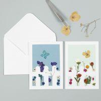 Un biglietto di auguri con fiori secchi dietro una staccionata