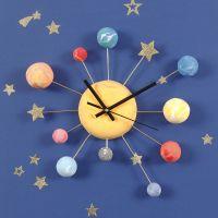 Un orologio da parete decorato con pianeti in Silk Clay, stickers a stella e filo da fiorista