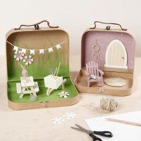 Piccole valigie trasformate in un giardino in miniatura con vernice, mobili in miniatura e accessori
