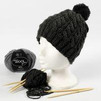 Un cappello lavorato a maglia con un motivo a trecce e un pom-pom